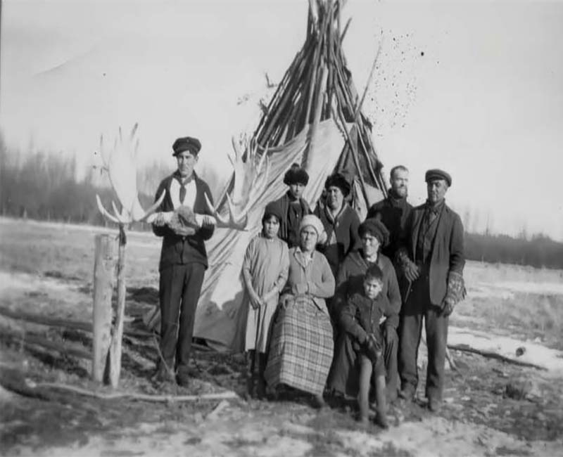 Group of people outside at Joussard St. Brunos school posing in front of teepee