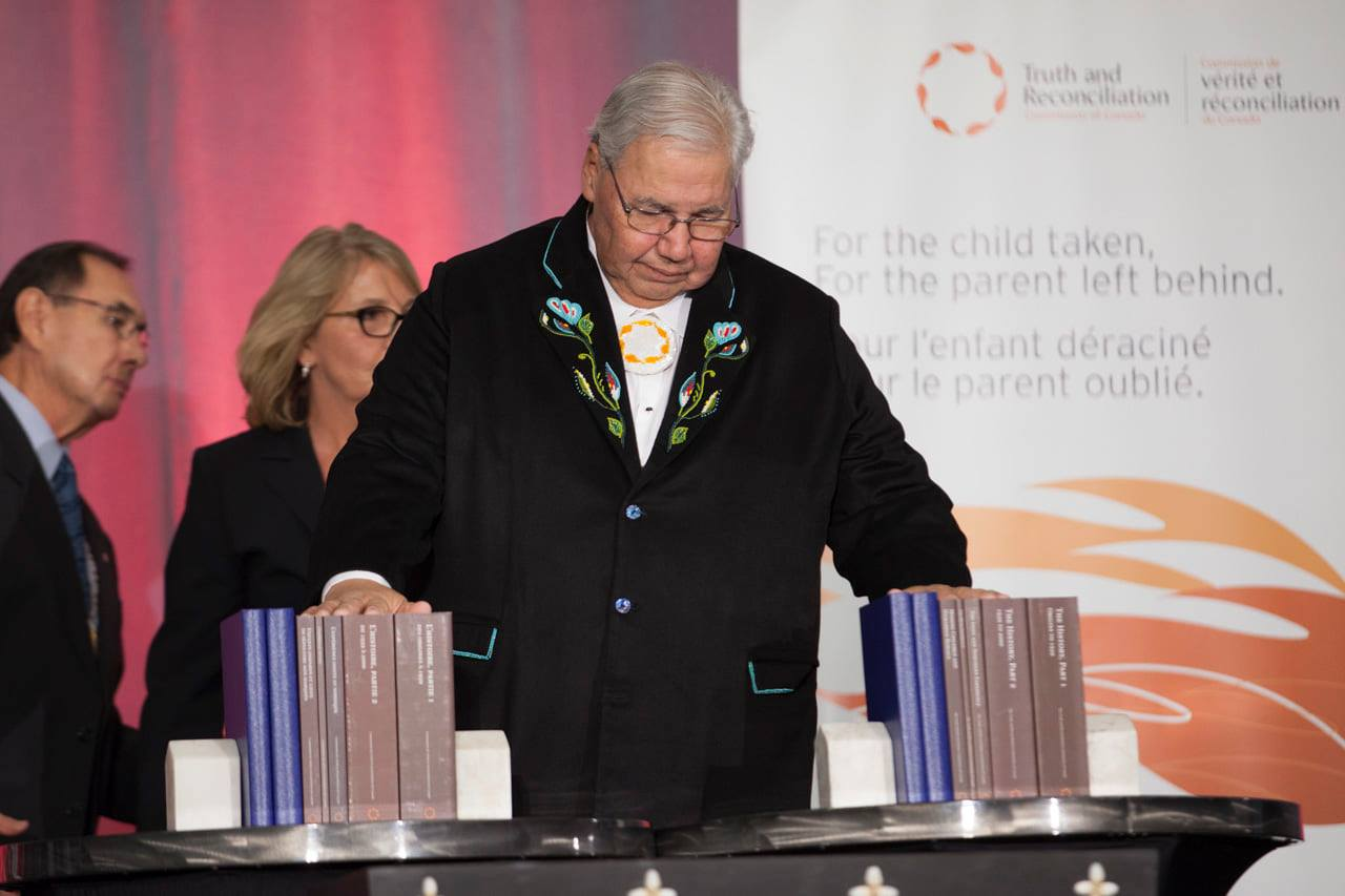 Person on stage with hands on report books at TRC closing ceremony