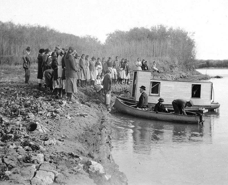 Group of people standing on shore with three people in a boat